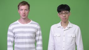 Two young multi-ethnic businessmen together against green background. Studio shot of young Asian businessman and young Scandinavian businessman together against stock video footage