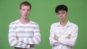 Two young multi-ethnic businessmen together with arms crossed. Studio shot of young Asian businessman and young Scandinavian businessman together against chroma stock video footage