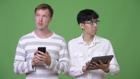 Two young multi-ethnic businessmen using phone and digital tablet for social media concept. Studio shot of young Asian businessman and young Scandinavian stock footage