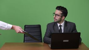 Two young multi-ethnic businessmen working together against green background. Studio shot of young handsome bearded Persian businessman and young handsome stock video footage