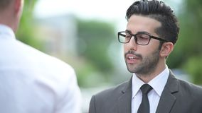 Two young multi-ethnic handsome businessmen together in the streets outdoors. Portrait of young handsome bearded Persian businessman and young handsome stock video