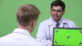Two young multi-ethnic man doctors having meeting. Studio shot of young Persian man doctor and young man doctor against chroma key with green background stock video footage