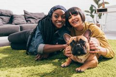 two young multicultural female friends laying on rug royalty free stock photos
