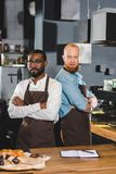 Two young multicultural male baristas in aprons standing with crossed arms. In coffee shop royalty free stock photo