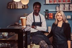 Two young multiracial baristas in aprons standing welcomingly at their trendy coffee shop. royalty free stock images