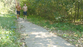 Two young muscular athletes running at the forest path. Active strong men training outdoors. Fit handsome athletic male Stock Photography