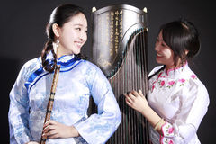 Two young musicians. Two Chinese musicians with bamboo flute and zither on dark Stock Photo