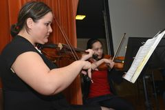 Two young women playing violins at a party royalty free stock images