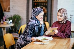 Two Muslim women in cafe, shop online using electronic tablet. Two young muslim business team with beautiful smile holding digital tablet while sitting in cafe Royalty Free Stock Photo