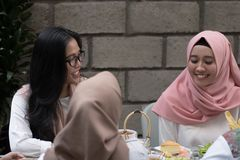 Two young muslim female having conversation while enjoying meal royalty free stock photo