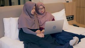 Two young muslim woman watch video on laptop in the bedroom stock video