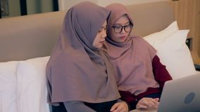 Two young muslim woman watch video on laptop in the bedroom stock footage