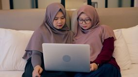 Two young muslim woman watch video on laptop in the bedroom stock video footage