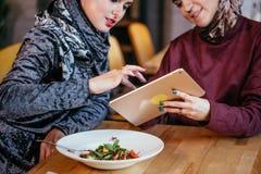 Two Muslim women in cafe, shop online using electronic tablet. Two young Muslim women in cafe, shop online using electronic tablet Stock Image