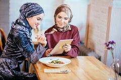 Two Muslim women in cafe, shop online using electronic tablet. Two young Muslim women in cafe, shop online using electronic tablet Stock Images
