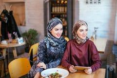 Two Muslim women in cafe, shop online using electronic tablet. Two young Muslim women in cafe, shop online using electronic tablet Stock Photos