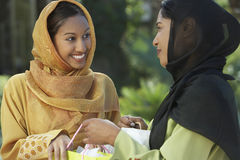 Two Young Muslim Women Talking Outdoors. Two happy young Asian Muslim women in traditional wear talking outdoors Stock Photos