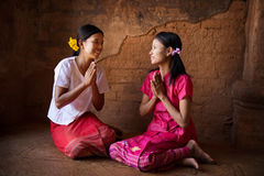 Two young Myanmar girls praying in temple Stock Photo