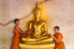 Two young novices monk scrubbing buddha statue at temple royalty free stock photography