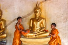 Two young novices monk scrubbing buddha statue at temple stock photo