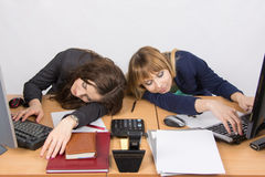 Two young office employee asleep on desk for computers Stock Images