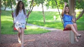 Two young omen swinging in summer park. Slow motion stock video
