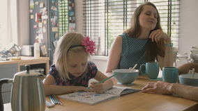 Two young parents having a conversation at the kitchen table while their daughter is colouring. Slow mo, Steadicam shot. Two young beautiful parents having a stock video footage