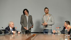 Two young partners entrepreneurs in front of big table make presentation of their new Internet startup to large audience