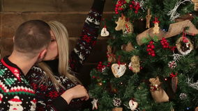 Two young peopes wearing xmas tree and kissing stock footage