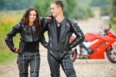 Two young people against motorbike Royalty Free Stock Photo