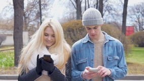 Two young people, a beautiful blonde and her friend, are walking down the street and using mobile phones. Write messages. In the messenger. Go out of the blur stock video footage