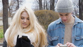 Two young people, a beautiful blonde and her friend, are walking down the street and using mobile phones. Write messages. In the messenger. Go out of the blur stock footage