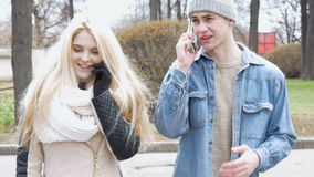 Two young people, a beautiful blonde and her friend, are walking down the street and using mobile phones. Write messages in the messenger. Go out of the blur stock video