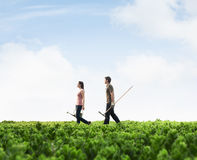Two young people carrying gardening equipment walking across a green field with plants Stock Photo