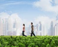 Two young people carrying gardening equipment walking across a green field with plants, cityscape in the background Royalty Free Stock Image