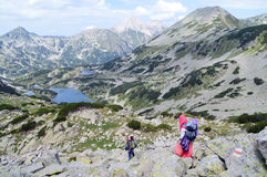 Two Young People Climbing Down on Stony Mountain Slop Royalty Free Stock Photos