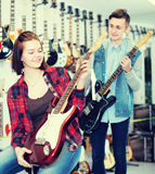 Two young people customers examining electric guitars Royalty Free Stock Photography