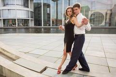 Two young people dancing tango outside on city embankment Stock Image