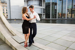 Two young people dancing tango outside on city embankment Stock Photos