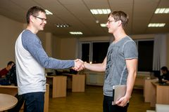 Two young people are discussing a project in the office. Shake hands with each other after the discussion and friendly smile stock images