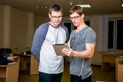 Two young people are discussing a project in the office. Standing next to each other, one of them tells the other about his projec stock photography