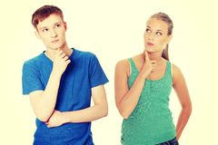 Two young people with finger on chin. Royalty Free Stock Images
