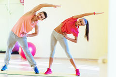 Two young people in the gym doing exercises for fitness Stock Images