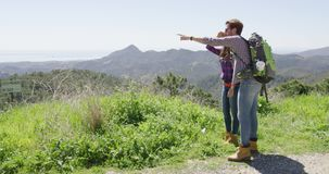 Two young people hiking in mountains stock video