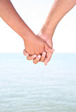 Two Young People Holding Hands by Water. Two Young People Holding Hands with Water as Background Stock Photo