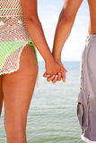 Two Young People Holding Hands by Water Stock Photo