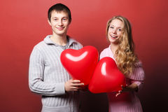 Two young people holding heart-shaped balloon Royalty Free Stock Images