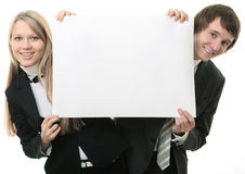 Two young people holding a white sign Royalty Free Stock Photos