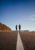Two young people jogging on country road Royalty Free Stock Photography
