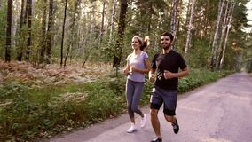 Two young people jogging together in the park full of green trees stock video footage